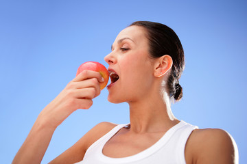 Brunette biting into tasty apple