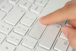 Hand pushing the button of grey keyboard