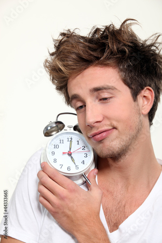 Sleepy man hugging his alarm clock