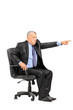 Angry boss sitting in armchair and pointing his finger