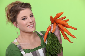 Woman holding bunch of carrots