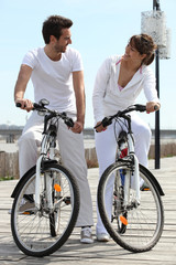Couple in white on a bicycle