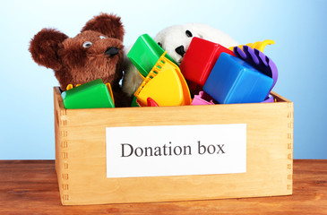 Donation box with children toys on blue background close-up