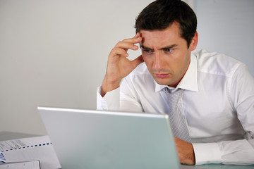 Businessman getting stressed at laptop