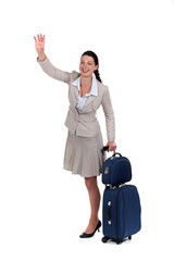 Woman with a suitcase waving at someone
