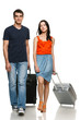 Full length of young couple walking with travel suitcases