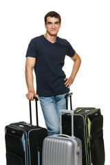 Young man standing with travel suitcases