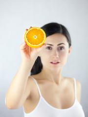 Piękna kobieta trzymająca w dłoni przekrojony owoc