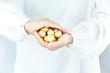Małe złote bombki na choinkę schowane w dłoni