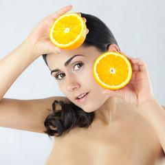 Młoda bardzo piękna kobieta schowana za owocami