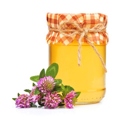 Honey in glass jars with clover flowers