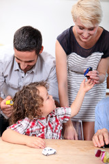 Family playing with a boy's toy cars