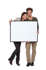 Trendy young couple stood with blank frame