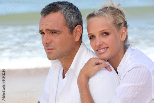 Couple dressed in white stood on beach