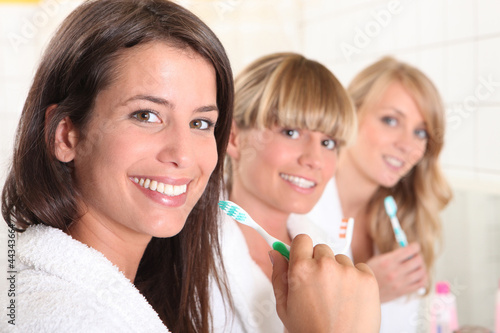 Three female house mates brushing their teeth
