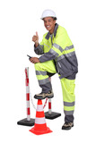 Man in high visibility overalls with a traffic cone and barrier