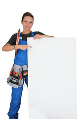 Woman pointing at blank board with toolbox