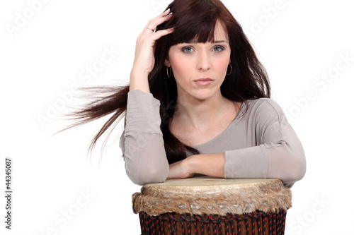 beautiful woman playing on traditional drums