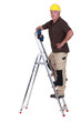 Mature handyman with drill climbing up ladder