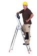 Mature handyman with drill climbing up ladder