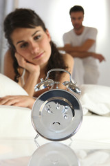 Couple staring at an alarm clock