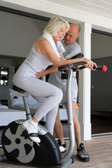 middle-aged blonde woman on exercise bike coached by husband