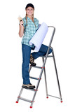 Women ladder climb with roll of wallpaper
