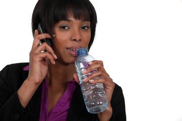Businesswoman drinking bottle of water