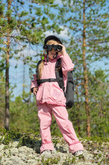 Little girl in a forest looking through binoculars