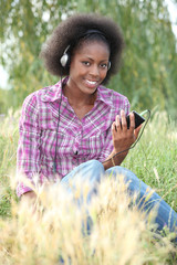 Teenager listening to music in field