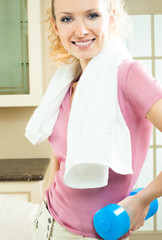 Woman with dumbbell and towel, at home