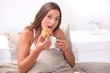 Woman eating a croissant in bed