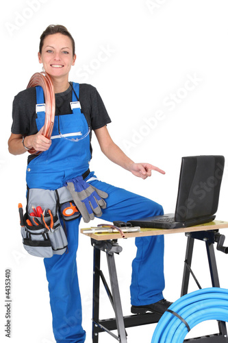 Female plumber surrounded by her equipment