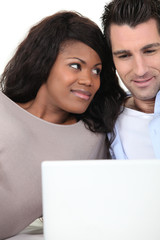 Couple at home looking at laptop