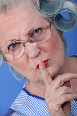 Elderly woman holding her finger up to her lips