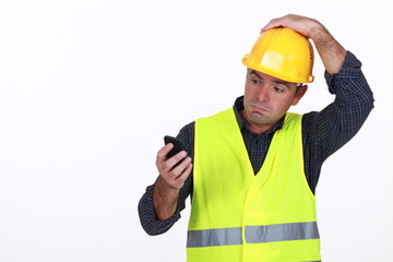 workman with fluorescent safety jacket looks puzzled