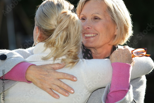 Adult daughter and mother hugging