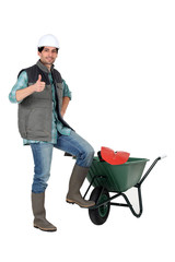 Man stood with wheelbarrow giving thumbs-up