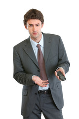 Unhappy businessman pointing on mobile phone
