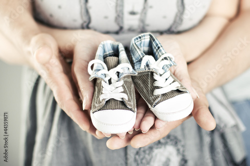 Newborn baby booties in parents hands