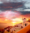 Santorini with windmill against sunset in Greece