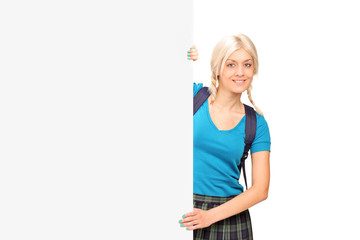 A female student posing behind a blank panel