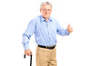 A senior man holding a cane and giving thumb up