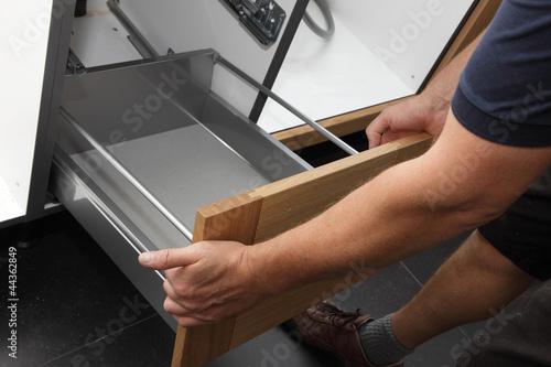 homme installant cuisine équipée