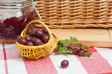 Basket with berries of a red gooseberry and jam