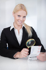 Businesswoman looking at check trough the loupe