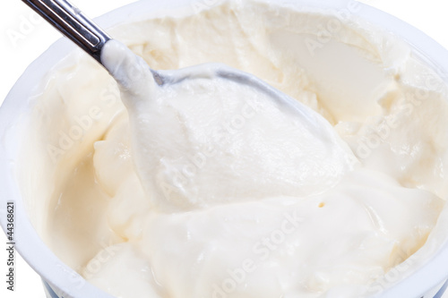metal spoon in tub of sour cream