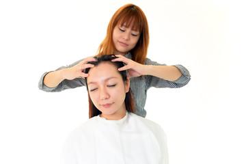 ヘッドマッサージをする美容師