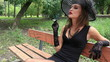 beautiful girl in a black dress smokes in park