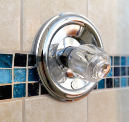 New shower handle with tile wall in beige and blue.